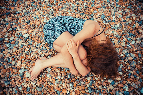 A young woman is lying curled up on a pebble beach